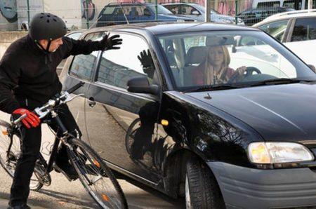 Radfahrer und Autofahrer kurz vor dem Zusammenprall
