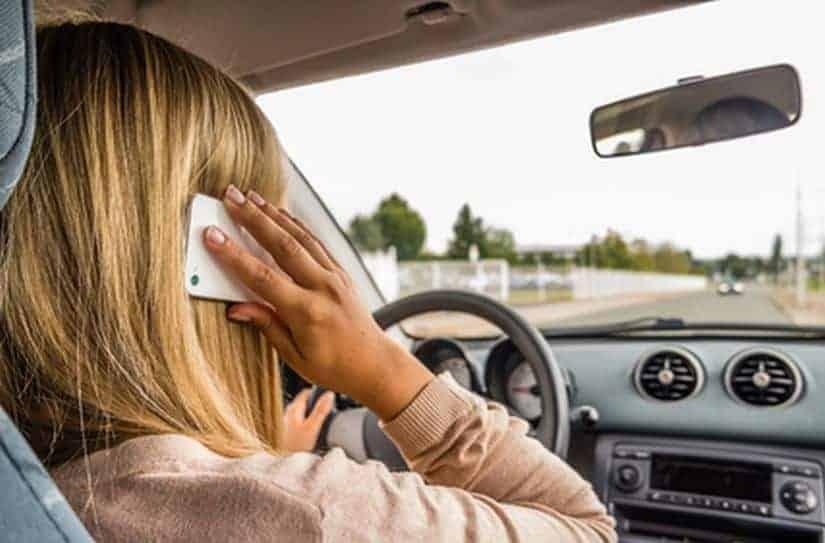 Junge Frau mit Handy am Steuer Gefahr