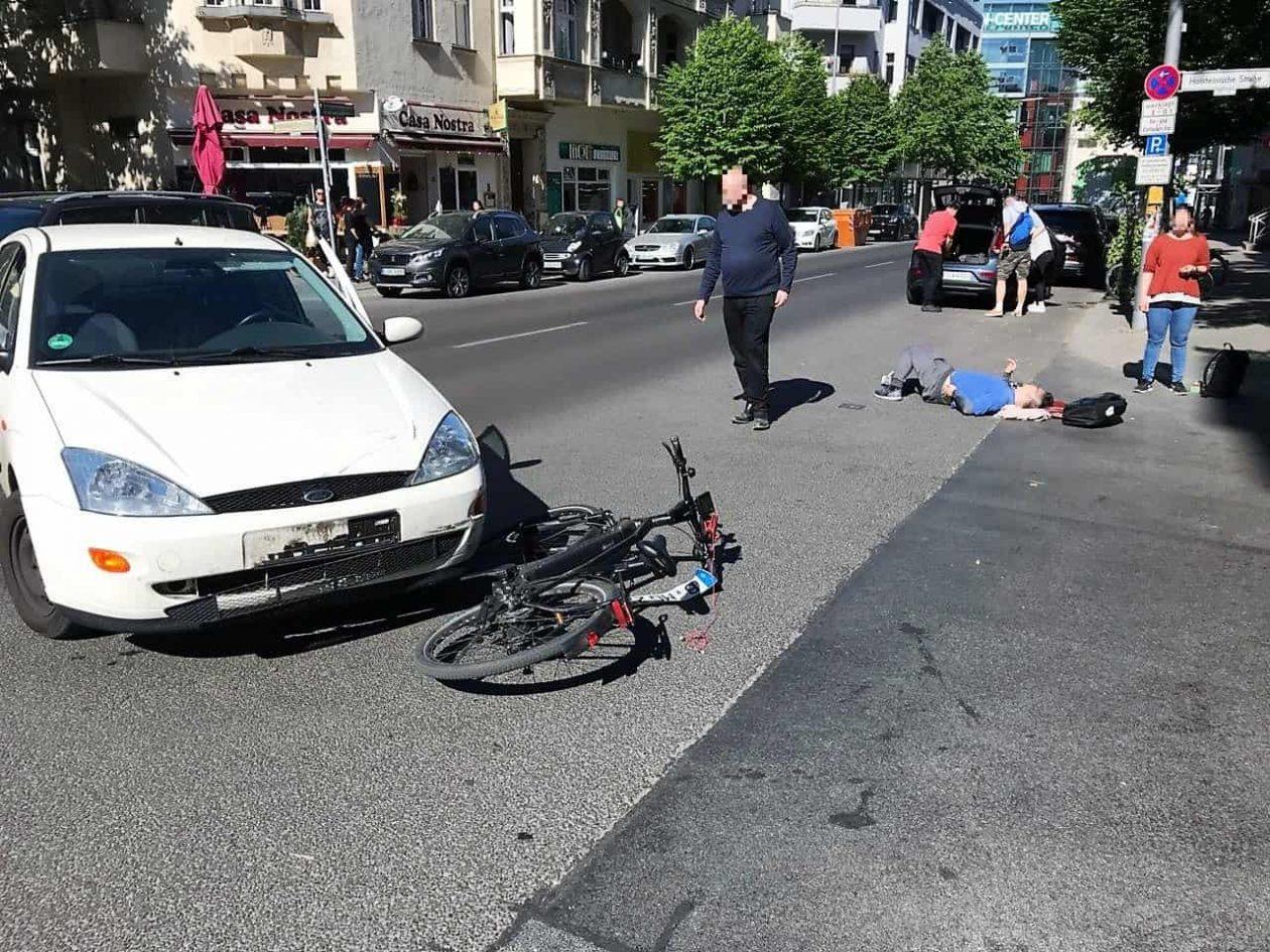 Ein Fahrrad liegt unter einem Auto. Der Fahrzeuglenker hat als Linksabbieger einen Fahrradfahrer übersehen. Dieser liegt aut der Straße und wartet auf die Feuerwehr.