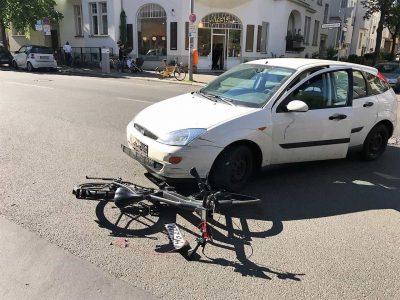 Ein Fahrrad liegt unter einem weißen Auto nach einem Autounfall (Linksabbieger)