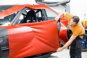 Werbetechniker bei Vollfolierung eines Sportwagens