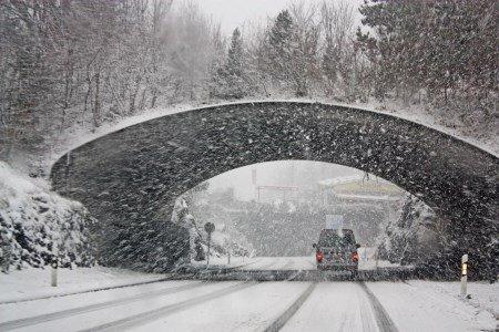Ein Auto bremst auf einer verschneiten Straße