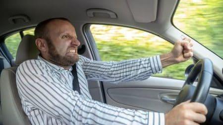 Agressiver Mann droht einem anderen Autofahrer.
