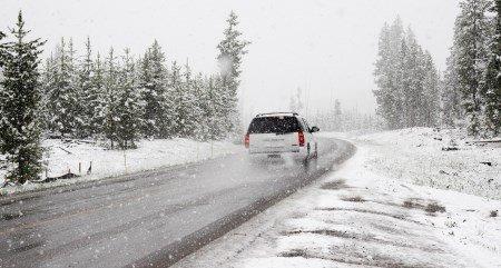 Ein Auto fährt durch eine verschneite Straße.