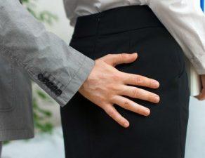Ein Mann berührt eine Frau am Po.