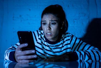 Eine Frau schaut erschrocken Bilder von sich, die ihr ein Erpresser geschickt hat, auf dem Handy an.