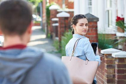 Eine junge Frau wird von einem Mann gestalkt.