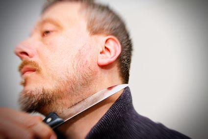 Ein Mann wird mit einem Messer am Hals bedroht.